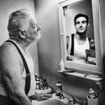 Reverse mentoring allo specchio: un uomo anziano fissa la sua immagine più giovane.