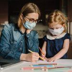 Una baby sitter e una bambina, entrambe con mascherina, mentre adoperano dei colori.