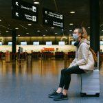 Un'expat in mascherina seduta sulla sua valigia in un aeroporto svizzero.