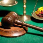 Diritto agroalimentare: un martello da giudice e una bilancia con frutta e ortaggi sul piatto
