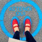 """Rischi del distanziamento sociale: una donna chiusa in un circolo sull'asfalto con la sigla """"aspetta qui""""."""