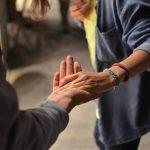 Un tutor sociale prende per mano una persona disabile.