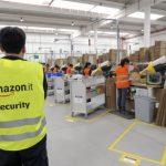 Amazon, è caporalato? L'interno di uno stabilimento del colosso americano, con un addetto alla sicurezza che controlla i lavoratori.
