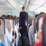 Sussidio di disoccupazione per piloti e hostess, la Svezia se ne lava le mani: una hostess cammina mestamente su un aereo pieno di passeggeri.