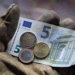 Questione salariale: pochi euro nella mano guantata di un operaio.
