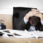 Malattie professionali: un uomo affranto in ufficio.