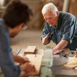 Convivenza tra generazioni: un artigiano anziano guida un lavoratore giovane