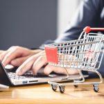 Spesa online: un carrello in miniatura vicino a un pc