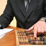 Mancanza di formazione nelle PMI familiari: un impiegato fa i calcoli con un pallottoliere.