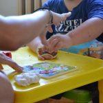Un'educatrice con un bambino autistico mentre giocano con la pasta modellabile.