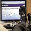 Diritto di critica, sui social è un lusso? Un uomo con scarpe eleganti tiene i piedi sul tavolo di fronte alla schermata iniziale di Facebook.