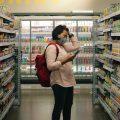 Una consumatrice in supermercato in mezzo a prodotti a Marca del Distributore.