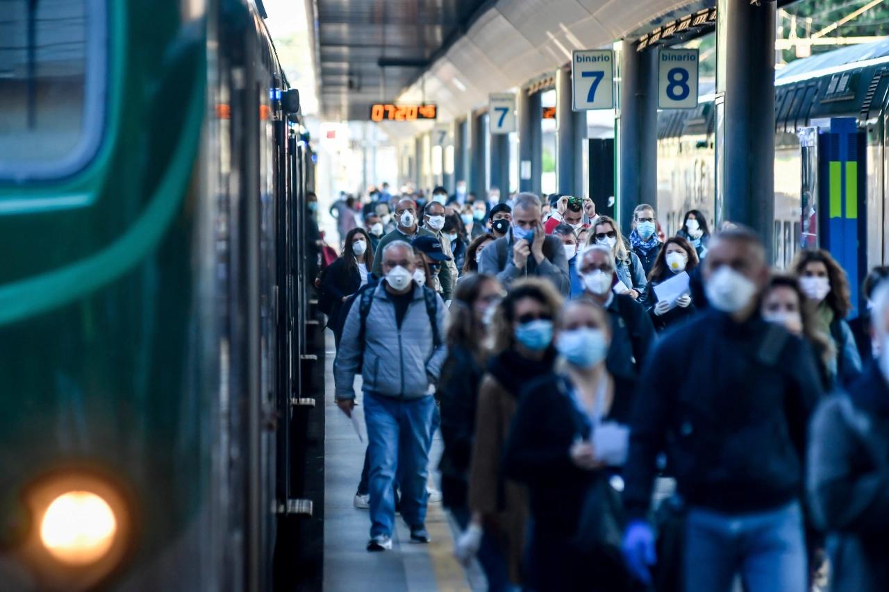 Dei pendolari in mascherina sul binario, senza controlli Green pass.
